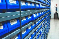 Blue plastic draws of stock / parts in rows of shelves stock photos