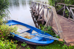 Blue plastic fishing boat stands near lake coast Royalty Free Stock Photo