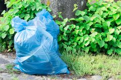 Blue garbage bag in garden, with green leaves. stock photos