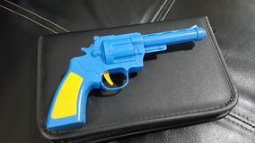 Blue plastic gun A yellow handle and trigger is placed stock images