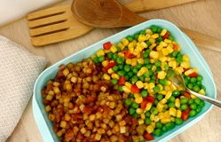 A lunchbox/plastic food container filled with vegetable mix and `pytt i panna` the swedish name for a dish with fried chopped/dice stock images