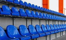 Blue plastic seats in the stadium. Tribune fans. Seats for spectators in the stadium royalty free stock image