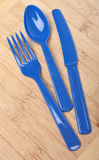 Blue Plastic Silverware on a Wooden Background Royalty Free Stock Images