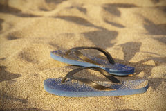 Blue plastic thongs in the sand Stock Image
