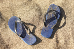 Blue plastic thongs in the sand Royalty Free Stock Images