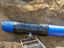 Blue plastic tubes in trench welded together with plastic pipes royalty free stock image