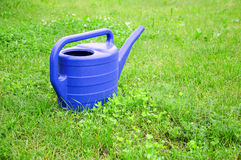 Blue plastic watering can on a green lawn Stock Photography
