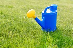 blue plastic watering can with a yellow lens on a green lawn. stock photography