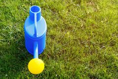 blue plastic watering can with a yellow lens on a green lawn. royalty free stock photo