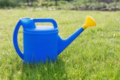 Blue plastic watering can with a yellow lens on a green lawn royalty free stock photography
