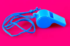 plastic whistle. A closeup of a blue plastic whistle on pink background Stock Photo
