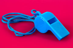 Blue  whistle. Closeup of blue plastic whistle isolated on pink background Stock Image