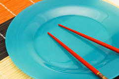 Blue plate and chopsticks. On the mat Royalty Free Stock Image