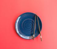 Blue plate with chopsticks Japanese style pink background. Royalty Free Stock Image