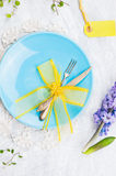 Blue plate with fork,knife and yellow table decoration Stock Photo
