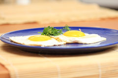 Blue plate with fried eggs Royalty Free Stock Image