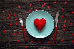 Blue plate with heart, red fork and knife on a dark wooden table Royalty Free Stock Image