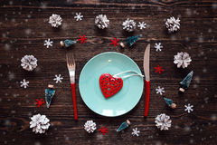 Blue plate with heart, red knife and fork, and christmas decorat Royalty Free Stock Photos