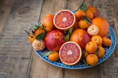 On a blue plate with oriental pattern fresh winter fruits - red oranges and mini tangerines. On a wooden background stock photos