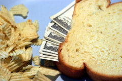 Blue Plate Special. American Money sticks out of a sandwich with chips on a blue plate royalty free stock image