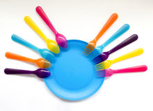 Blue plate surrounded by color forks and spoons, interesting bac Royalty Free Stock Image