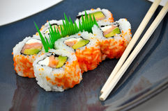 Blue Plate With Sushi Appetizer and Chopsticks. Sushi Philly rolls on a square blue plate with chopsticks.  Some fancy grass garnish in the middle.  The rolls Stock Photo