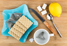 Blue plate with wafers and tea bags, sugar, lemon, teacup Stock Photo