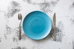 Blue Plate on white wooden background with utensils Royalty Free Stock Photos