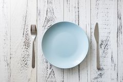 Blue Plate on white wooden background with utensils. Blue Round Plate with utensils on white wooden table background stock photo