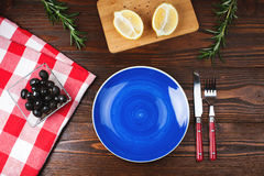 Blue plate on wooden table. Blue plate with fork and knife, on  wooden table with olives, lemon and rosemary Royalty Free Stock Images