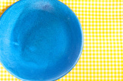 Blue plate on yellow checkered tablecloth Stock Image