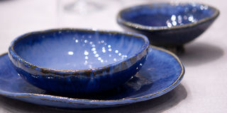 Blue plates and bowls on the table Royalty Free Stock Photography
