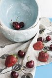 Blue plates with red juicy strawberries and delicious cherries. On a blue wooden background Royalty Free Stock Photos