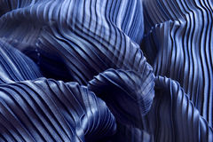Blue pleat fabric background is a beautiful curved wave. Stock Image