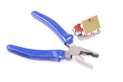 Blue pliers and little house over white. stock images