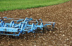 A blue plough in the field Royalty Free Stock Image