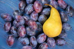 Blue plums and pear Stock Image