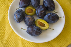 Blue plums on white plate Royalty Free Stock Photography