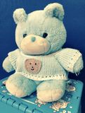 A blue plush bear with clothes sitting on a stool. stock photography