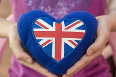 Blue plush heart with the UK flag in his hand. England is in your hands. UK favorite country. London Royalty Free Stock Photo
