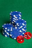 Blue poker chips and two cubes on the green table Stock Image
