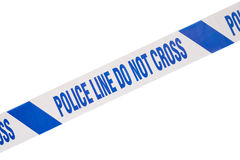 Blue police crime scene tape and white copy space. Blue, angled police line do not cross crime scene tape close up and white copy space Royalty Free Stock Photo