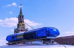 Blue police siren against the background of the Kremlin in Moscow. Police flasher on the background of the Spasskaya Tower of the. Moscow Kremlin royalty free stock photo
