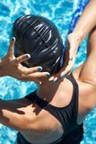 Blue polish nails swimmer placing cap Royalty Free Stock Images