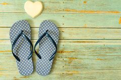 Blue flip flops beach and white porcelain heart on a wooden floor. Concept of holidays stock image