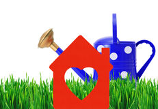 Blue polka dot watering can and house symbol on green grass Stock Photos