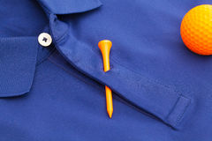 Blue polo shirt and orange golf ball. Detail of blue polo shirt and orange golf ball and wooden tee Royalty Free Stock Photography