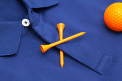Blue polo shirt and orange golf ball. Detail of blue polo shirt and orange golf ball and wooden tees Stock Photography