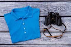 Blue polo t shirt and binoculars. Wooden desk surface background Royalty Free Stock Image