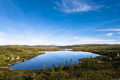 Blue Pond. A Reflective Pond set in Highlands with Glacial Drop Stones on Sunny Day Royalty Free Stock Photo